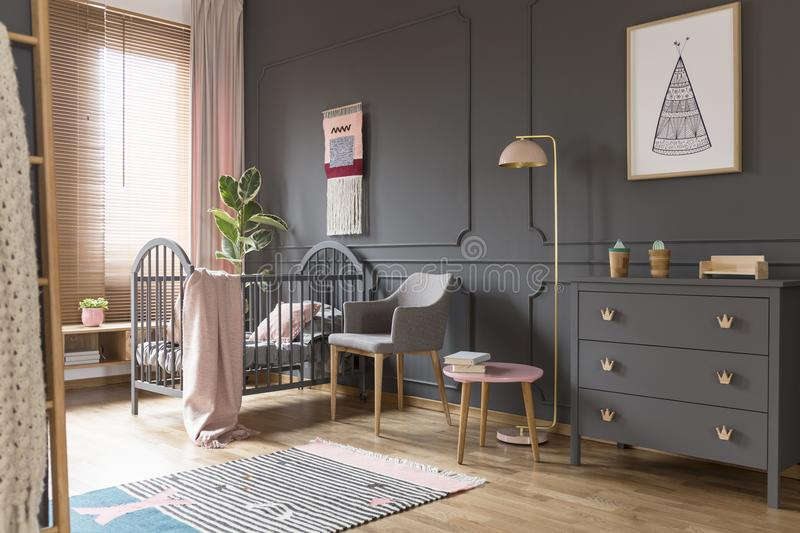 Grey cabinet next to pink lamp in simple baby`s bedroom interior stock photo