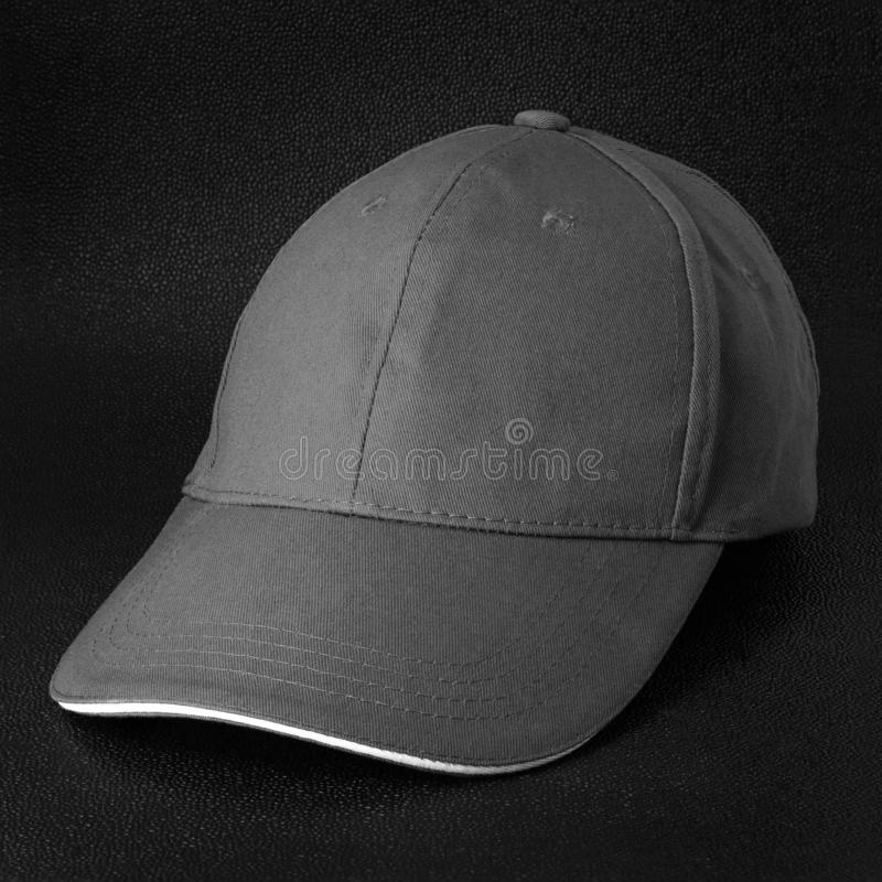 Grey cap on dark background. Template of baseball cap in side view. Grey cap royalty free stock photos