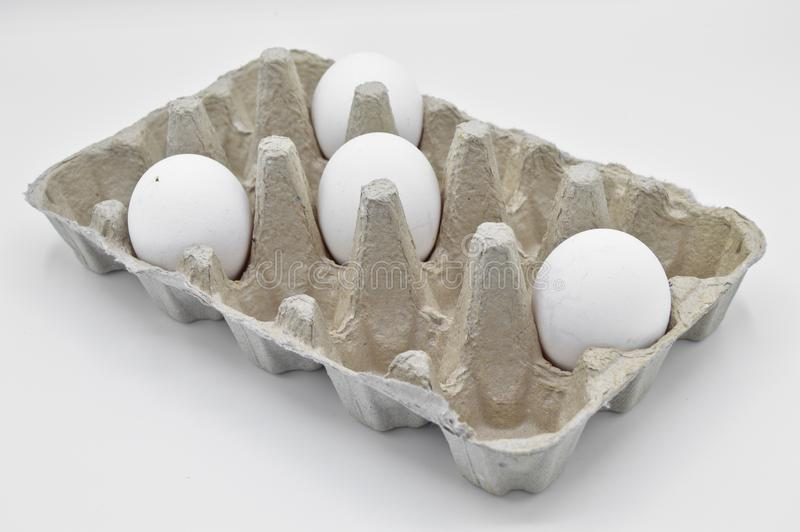 Grey cardboard and fresh raw chicken eggs royalty free stock images