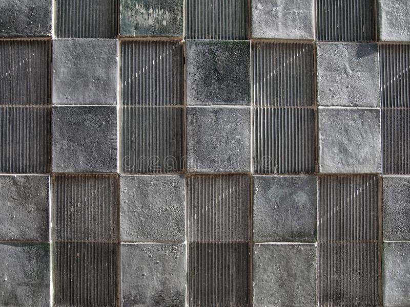 Grey concrete wall with geometric square pattern and distressed textures stock image