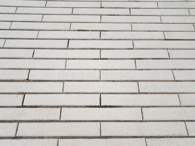 Grey cement rectangle tiles on ground or floor royalty free stock images