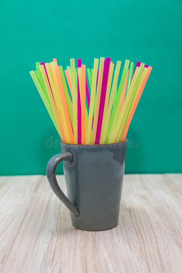 Ceramic Mug Filled With Plastic Straws of Several Colors stock images