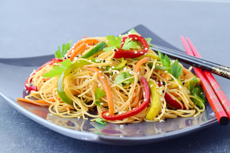 A grey ceramic plate with noodles and vegetables on a grey abstract background. Asian food. Healthy eating concept. A grey ceramic plate with noodles and stock image