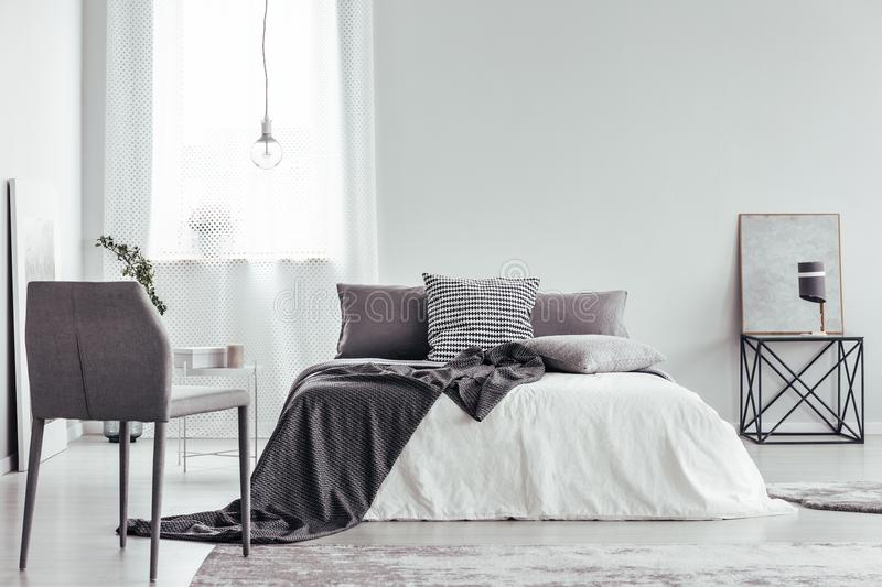 Grey chair in white bedroom. Grey chair and bed with patterned cushions and blanket in white bedroom interior with lamp on table against a wall with copy space stock images