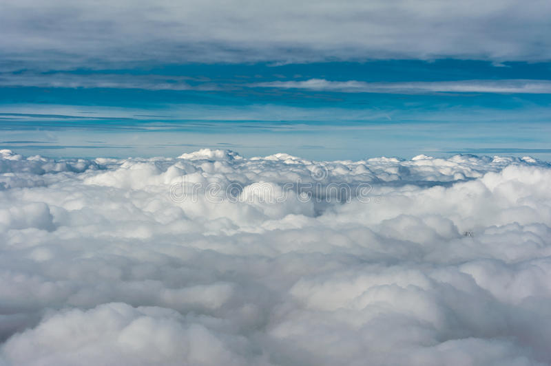 Grey cloud cover seen from above aginst blue sky horizon. Grey cloud cover hovering low over valley seen from above with blue sky on horizon royalty free stock photography
