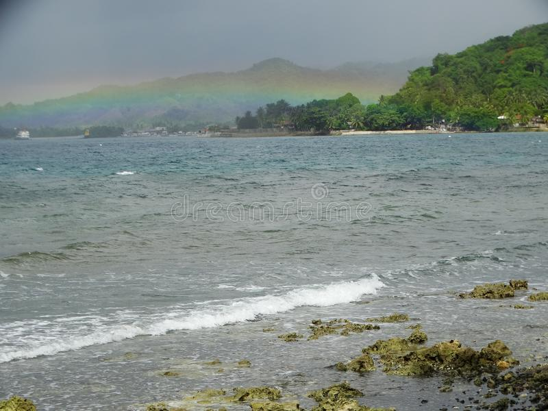 Cloudy sky and rainbow over the tropical island. Grey clouds and green plants on the tropicalnisland, with a beautiful rainbow. Jagna, Bohol, Philippines royalty free stock photos