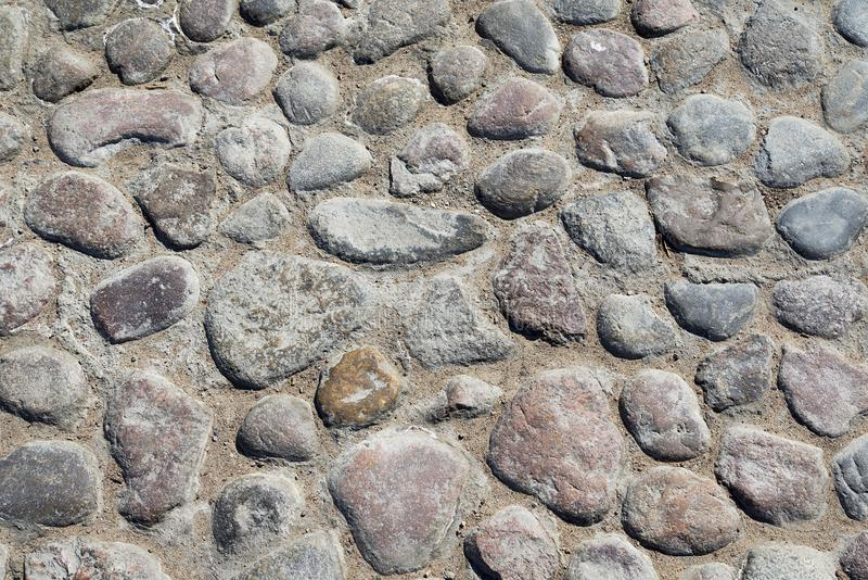 Grey cobblestone texture of a ground with many stones royalty free stock image