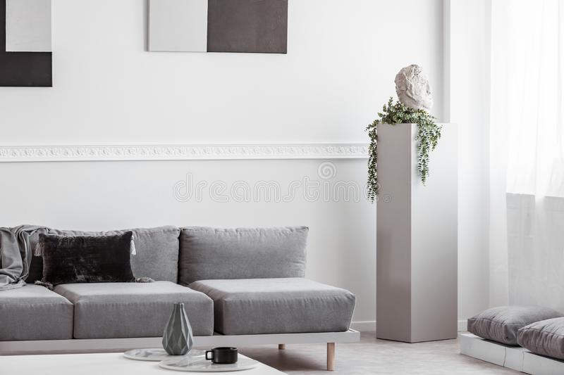 Grey concrete column with head and green flower in monochromatic living room interior stock photography