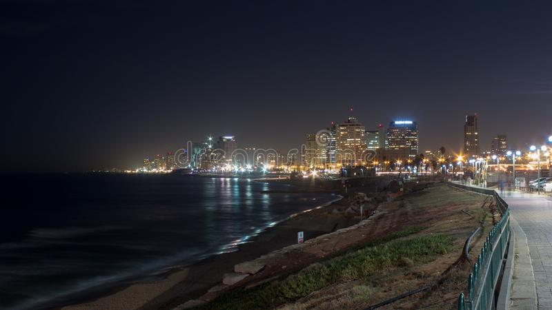 Grey Concrete Way Near Body of Water Leading to City during Nighttime stock image