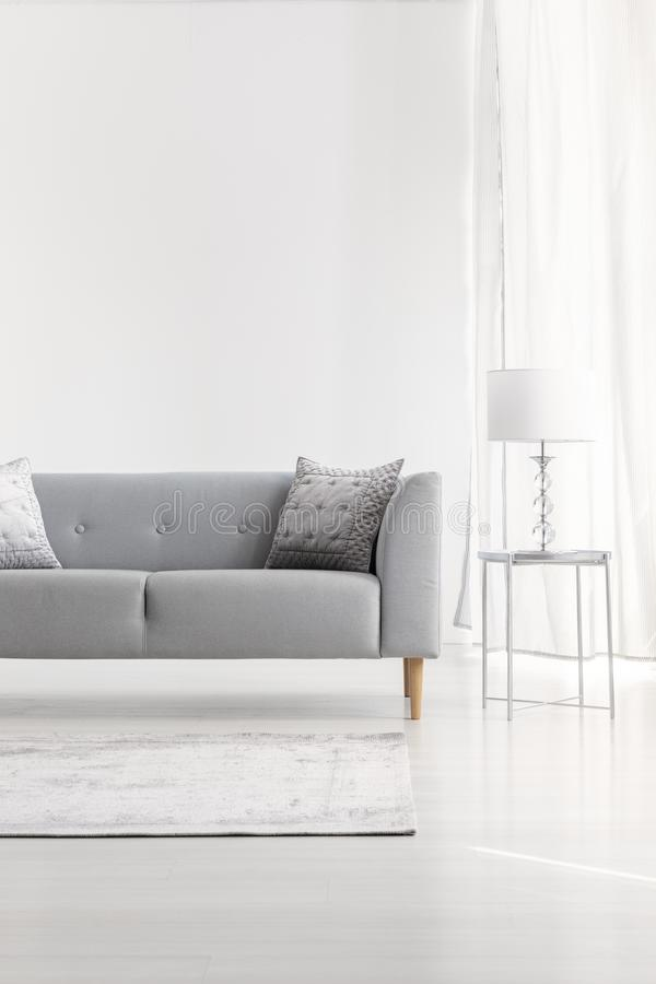 Grey couch next to lamp on silver table in white flat interior with copy space on empty wall. Real photo royalty free stock photo