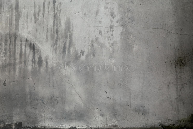 Grey cracked wall texture with the dirt and stains. Aged cement wall texture. The texture of the grey cement wall with dirty stains and cracks. Plaster cracked royalty free stock photos