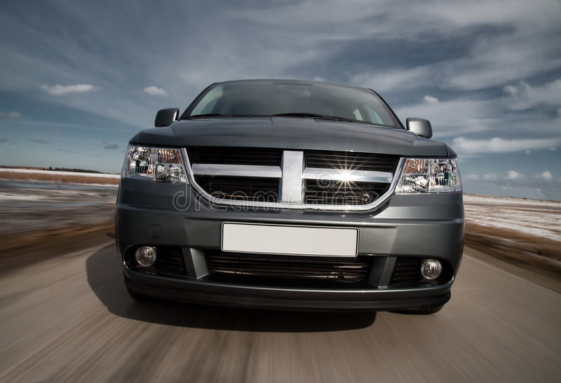 Grey crossover driving fast. Front view of fast driving crossover stock images