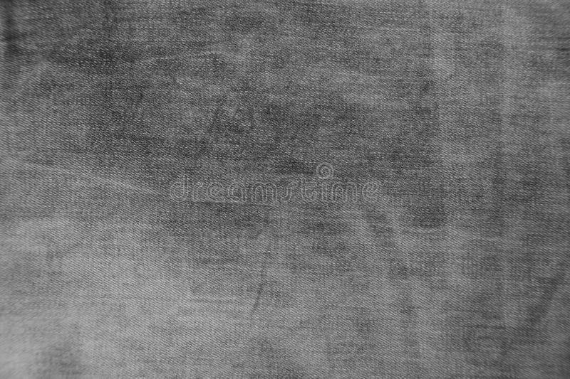 Grey denim jeans with stripes texture background. Black denim jeans texture / pattern background. Close up from pants stock image