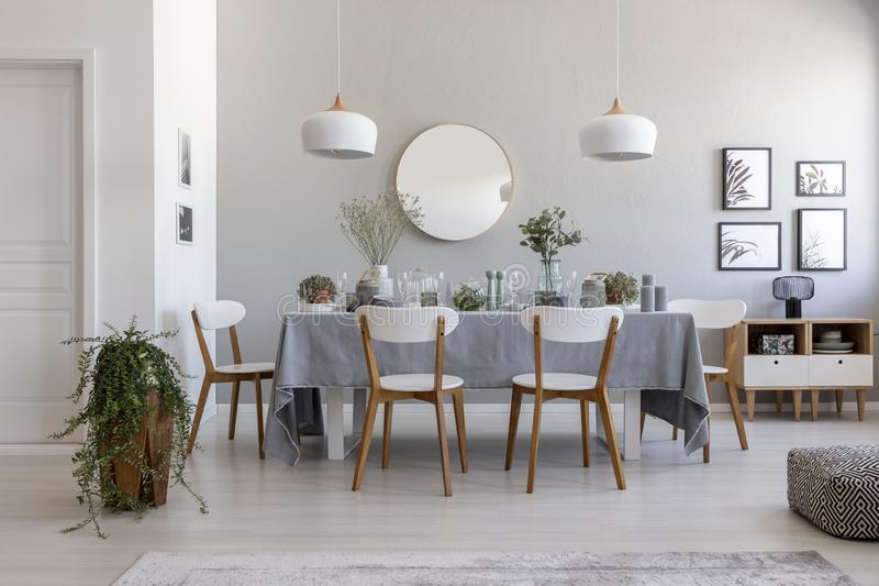 Grey dining room interior with a table, chairs and plant. Idea for a dinner stock photos