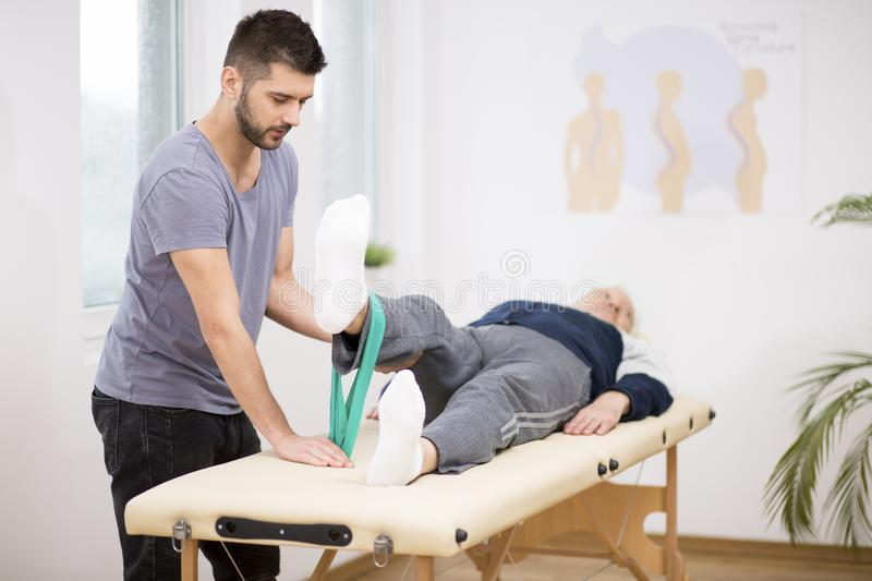 Grey elderly man lies on a table, and young doctor helps him during exercises royalty free stock images