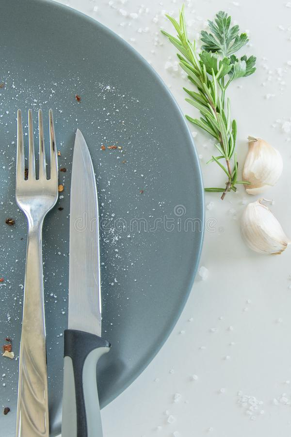 Grey empty ceramic plate with herbs knife and fork on salty white background. Minimal design. Space for text. Or menu stock image