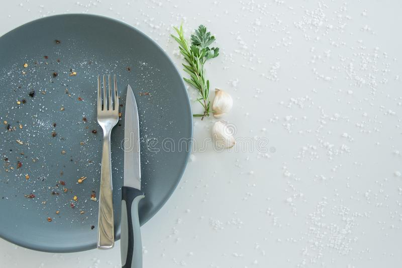 Grey empty ceramic plate with herbs knife and fork on salty white background. Minimal design. Space for text. Or menu royalty free stock image