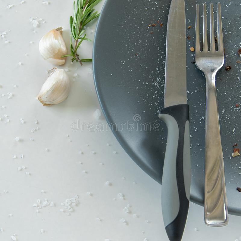 Grey empty ceramic plate with herbs knife and fork on salty white background. Minimal design. Space for text. Or menu royalty free stock images