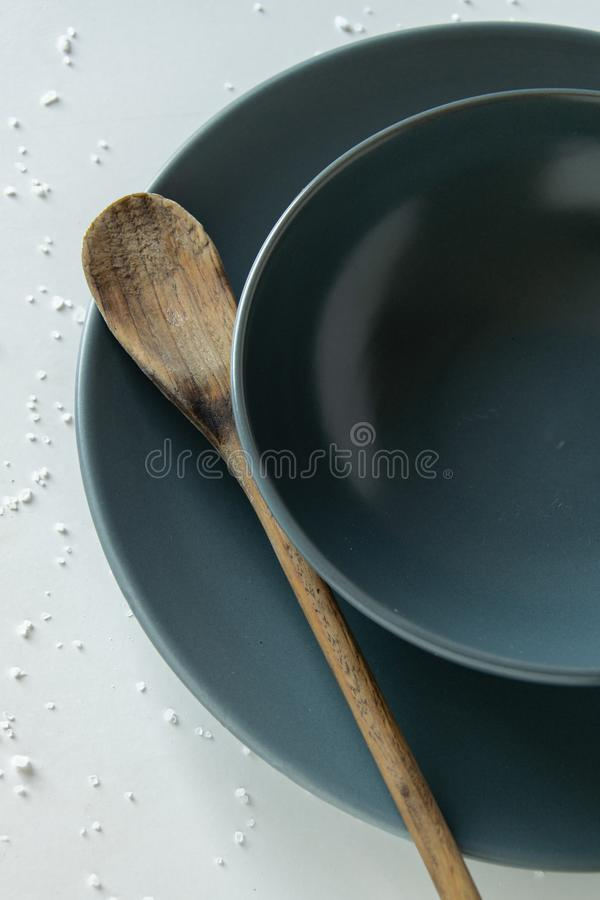Grey empty ceramic plate with wooden spoon on salty white background . Minimal design royalty free stock photos