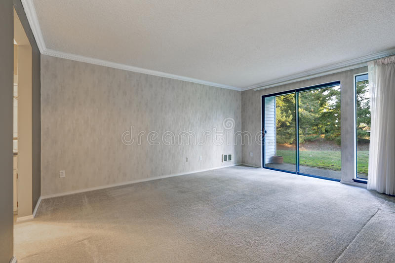 Grey empty room with metallic wallpaper. Carpet floor and glass sliding doors leading out to backyard. Northwest, USA stock photography