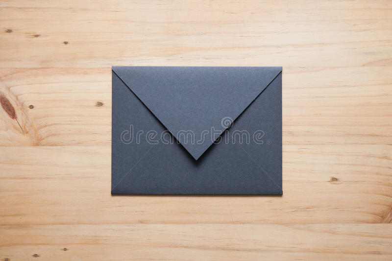 A grey envelope on the wood desk,. Top view at the studio royalty free stock image