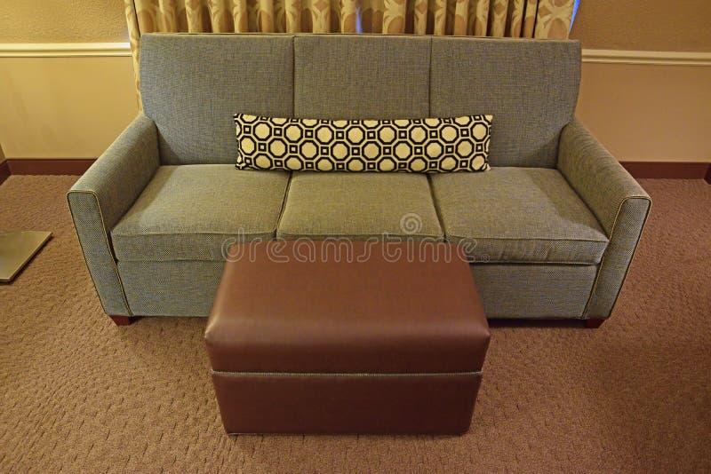 Grey Fabric Sofa met Bruine Leerottomane en lang smal hoofdkussen stock foto's