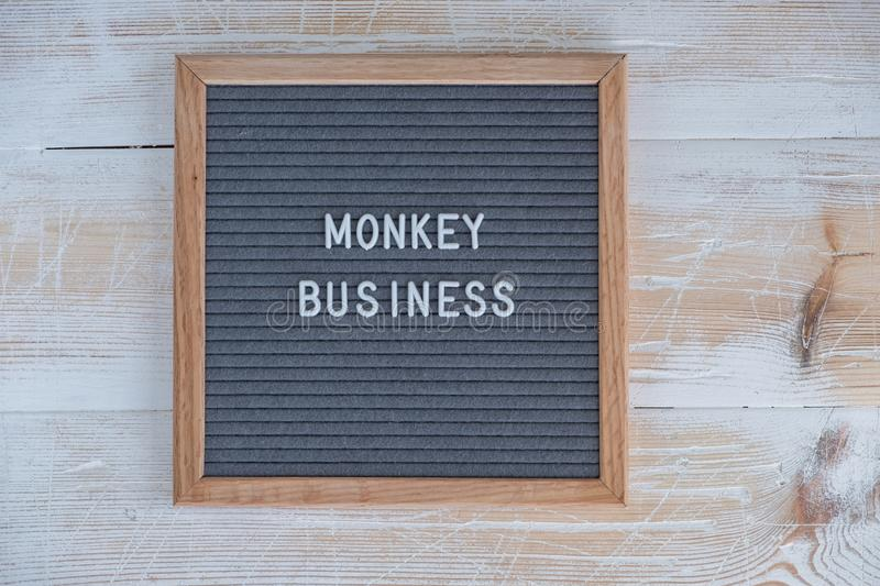 grey felt Board with English text monkey business royalty free stock images