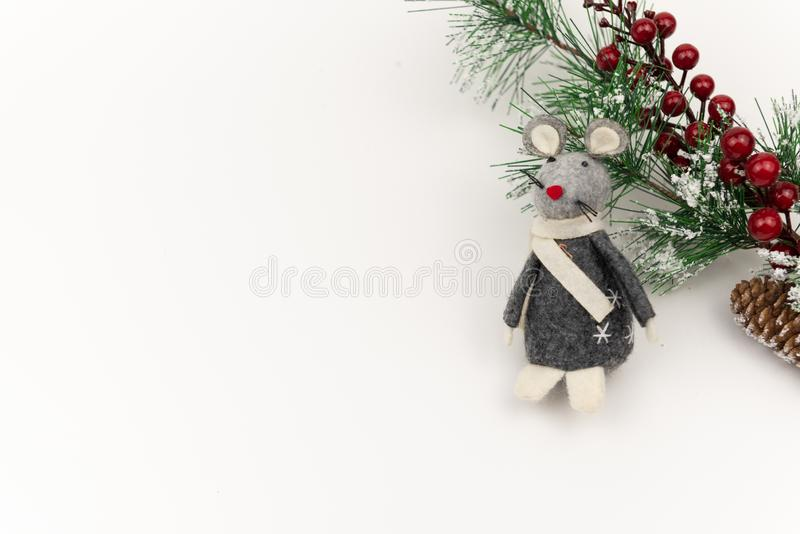 Grey felt toy rat with decorative fir tree with red berries on white background. Winter holidays backdrop composition . Minimalism royalty free stock image
