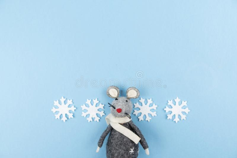 Grey felt toy rat with snowflakes on light blue background. Winter backdrop. Symbol of 2020 on Chinese calendar. Minimal style. royalty free stock images