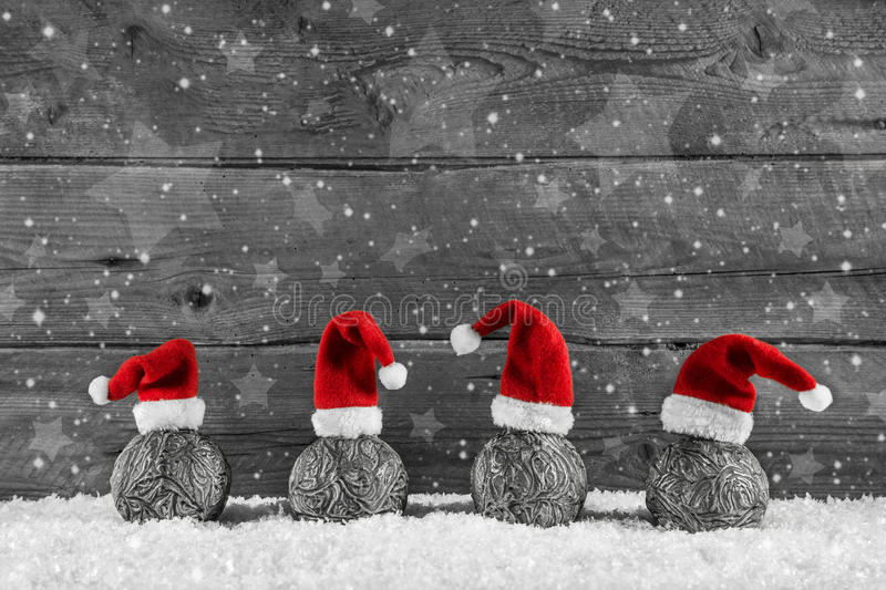 Grey festive wooden christmas background with four santa hats on royalty free stock photography