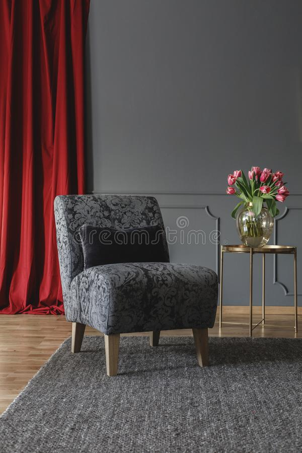 Grey floral chair with black cushion standing on dark carpet in elegant room interior with fresh tulips on gold metal table and re royalty free stock image