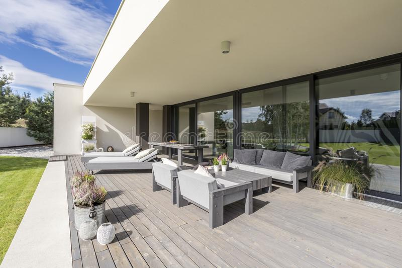 Grey garden furniture on board floor royalty free stock photography