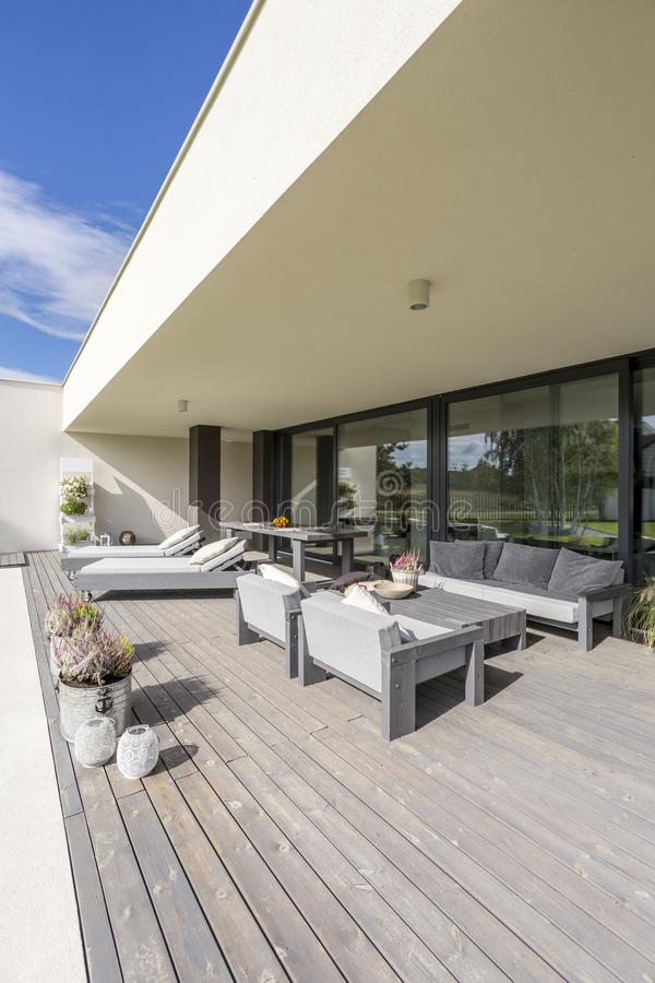 Grey garden furniture on terrace. Grey garden furniture on board floor with flowers in pots on terrace of spacious mansion stock image