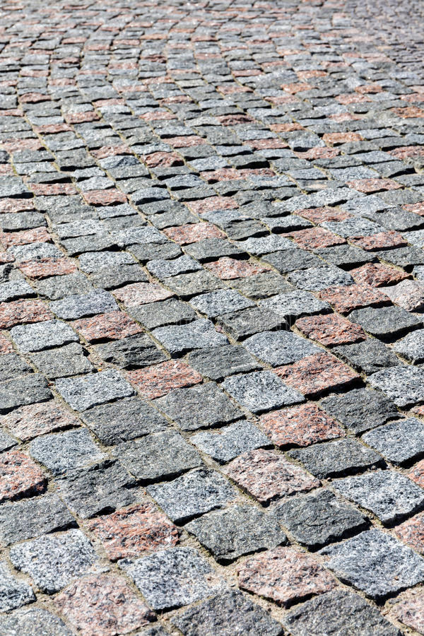 Grey granite cobblestone pavement background with uneven surface stock photography