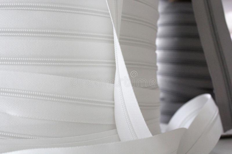 Grey and gray zipper for clothes. Clasp for clothes. White zipp in focus. stock image
