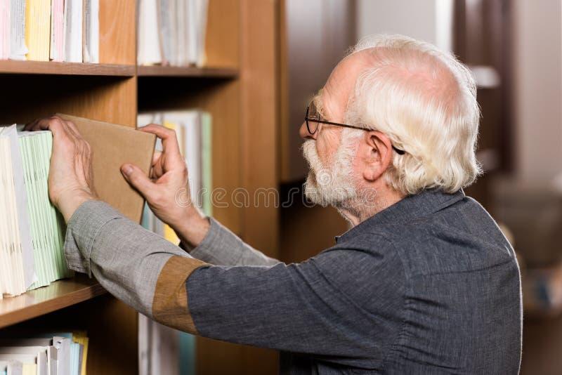 grey hair librarian taking book stock photos
