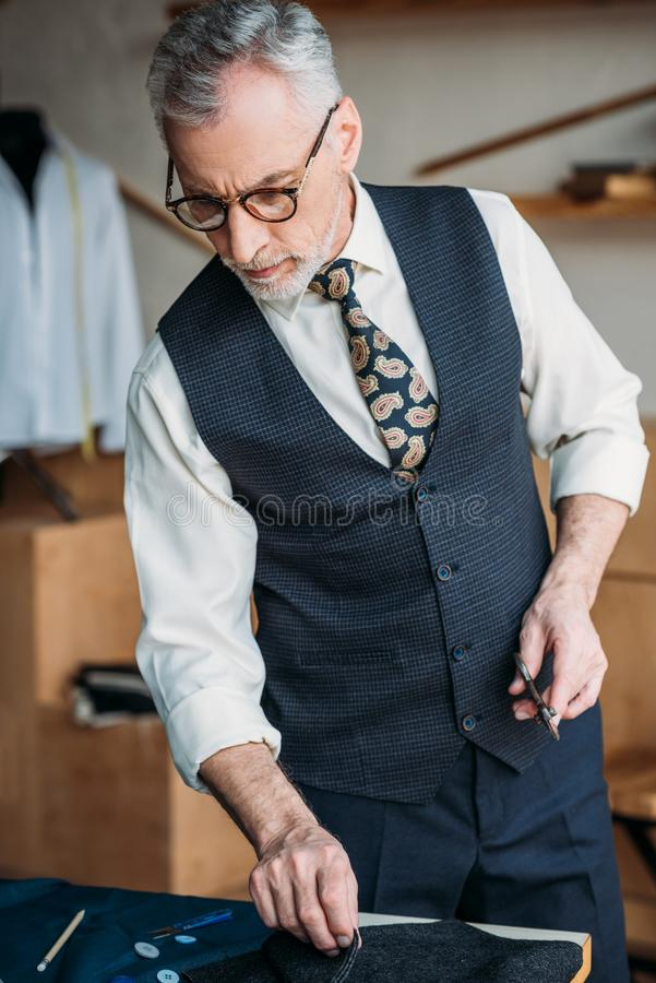 Grey hair tailor examining cloth. At sewing workshop stock photography