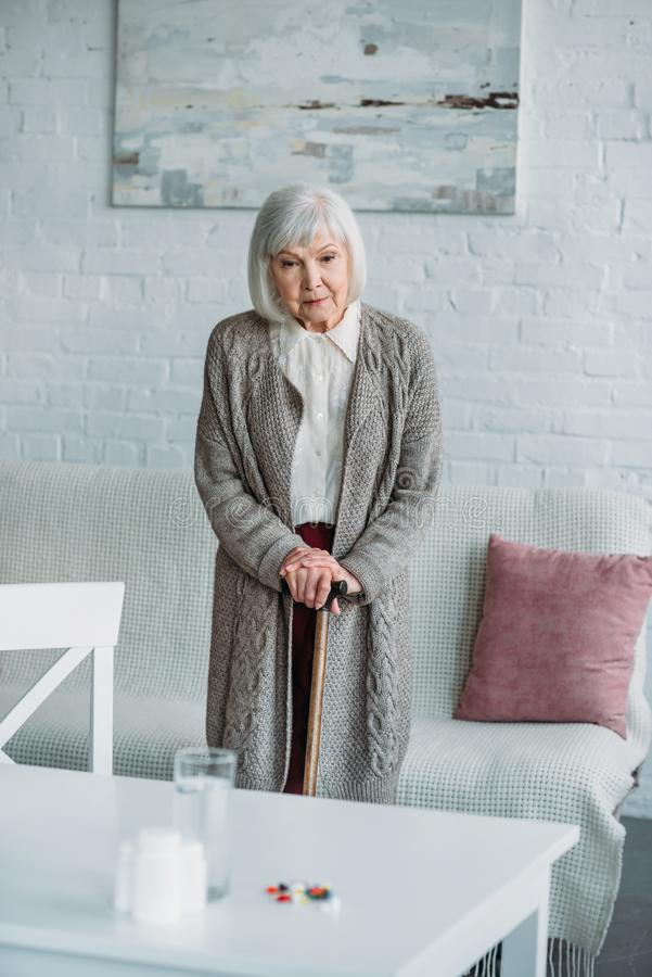 grey hair woman with walking stick standing in room with medicines on tabletop stock images