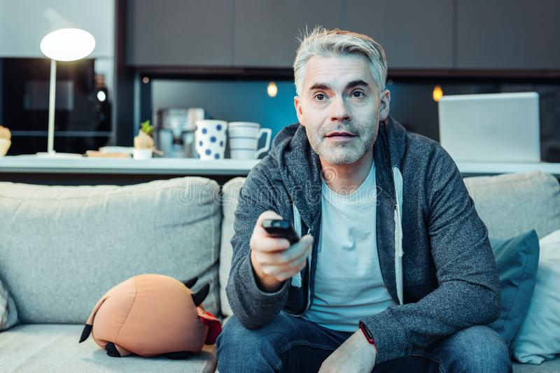 Grey-haired bearded attractive man in sportswear watching tv royalty free stock images