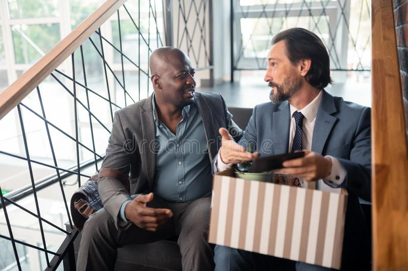 Grey-haired bearded man speaking with colleague after been fired royalty free stock images