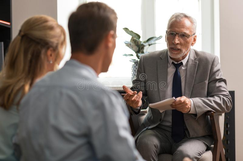 Grey-haired Caucasian senior psychologist talking to a couple royalty free stock images