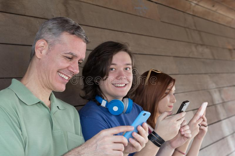 Grey haired dad and children: boy and girl looking at screen of royalty free stock image