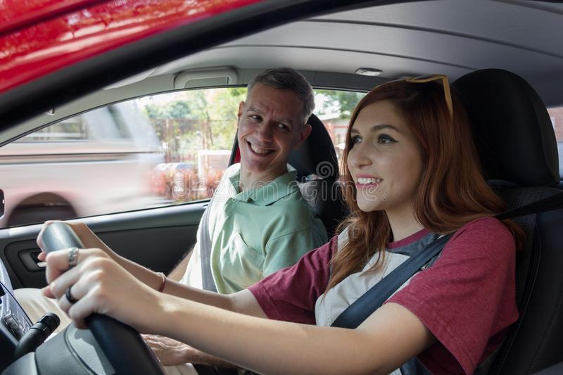 Grey haired dad is teaching daughter how to drive. Concept of family, paternity. Grey haired dad is teaching daughter how to drive. Driving lessons. Concept of royalty free stock images