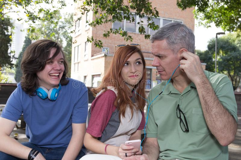 Grey haired dad with teen daughter and son are listening to music. Father Day. Concept of family, different stock images