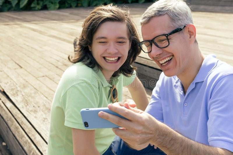 Grey haired dad and teenager son are looking at screen of mobile stock photo