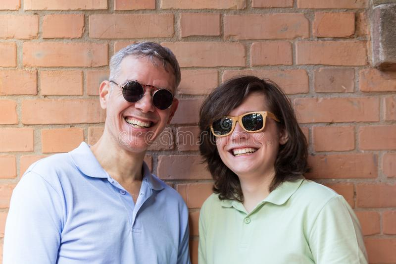 Grey haired dad and teenager son wearing sunglasses and looking away. Fathers Day. Concept of family, enjoyment, fatherhood, royalty free stock images
