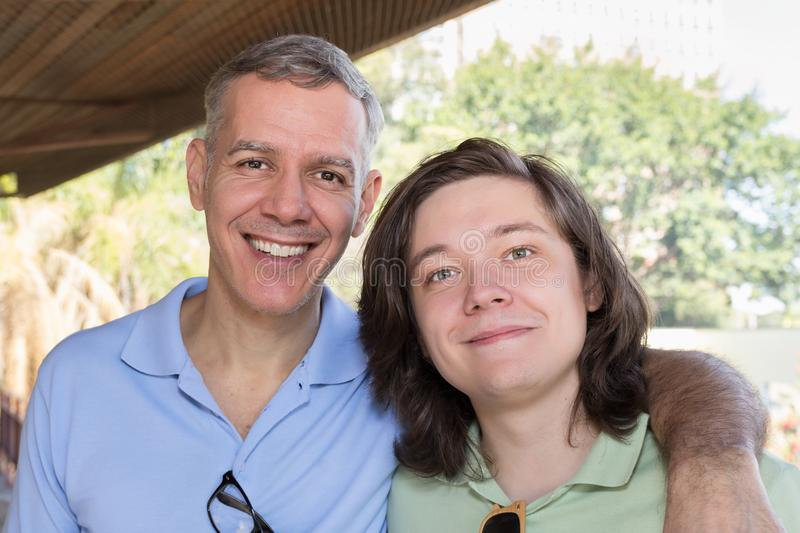 Grey haired dad and young adult son smiling. Father Day. Concept royalty free stock photography