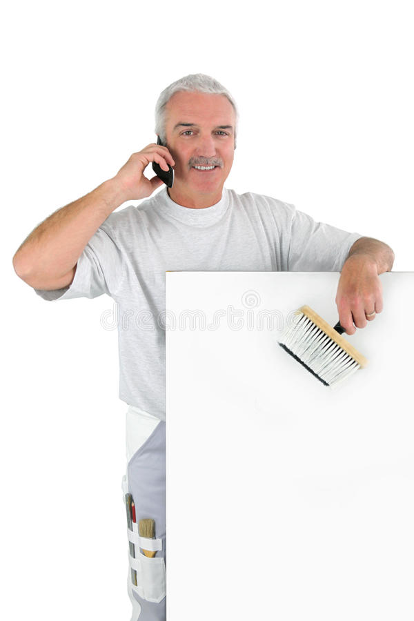 Grey-haired decorator. Stood with brush and mobile telephone royalty free stock photos