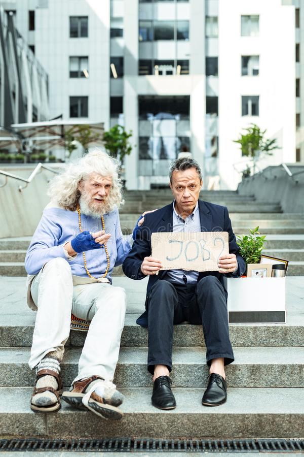 Grey-haired dismissed man sitting near case with personal belongings. Why dismissed. Grey-haired dismissed men feeling extremely bewildered while sitting near royalty free stock photos
