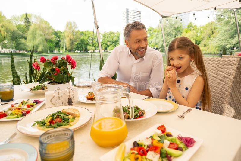 Grey-haired grandfather smiling looking at girl eating bruschetta stock photo
